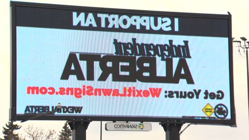 a white sign with black text: A Wexit Alberta billboard encourages an independent Alberta from Canada.