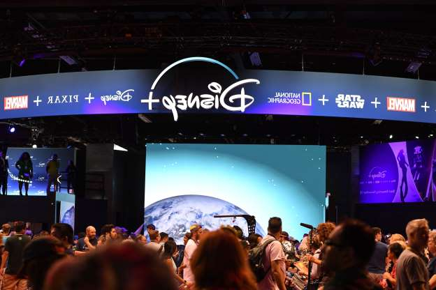 Attendees visit the Disney+ streaming service booth at the D23 Expo, billed as the