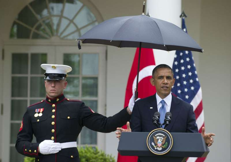 Barack Obama in a military uniform: A US Marine holds an umbrella for US President Barack Obama during a brief rain shower as he hold a joint press conference with Turkish Prime Minister Recep Erdogan in the Rose Garden.