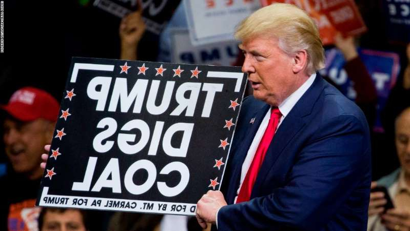 Donald Trump holding a sign: Republican presidential nominee Donald Trump  holds a sign supporting coal during a rally at Mohegan Sun Arena in Wilkes-Barre, Pennsylvania on October 10, 2016. / AFP / DOMINICK REUTER        (Photo credit should read DOMINICK REUTER/AFP/Getty Images)