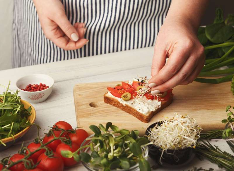food on the cutting board: Chef adding toppings to toast for a high cholesterol diet plan