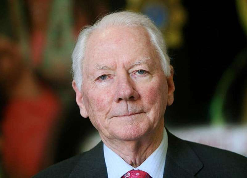 Gay Byrne wearing a suit and tie smiling at the camera