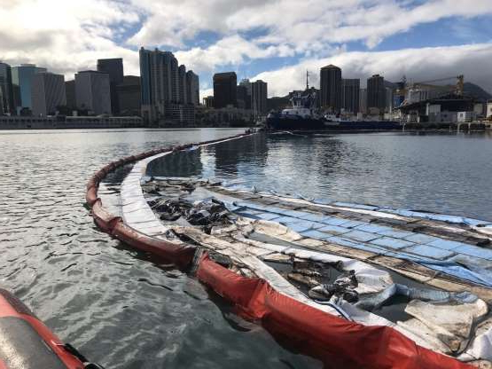 In this photo provided by the U.S. Coast Guard, their crews and other local agencies respond to an oil discharge from vessel Kamokuiki at Pier 19 in Honolulu, Thursday, Nov. 7, 2019. Two response vessels arrived on scene and deployed 1,600 feet of hard boom surrounding the 25 bales of absorbent material. (Petty Officer 2nd Class James Connor/U.S. Coast Guard via AP)