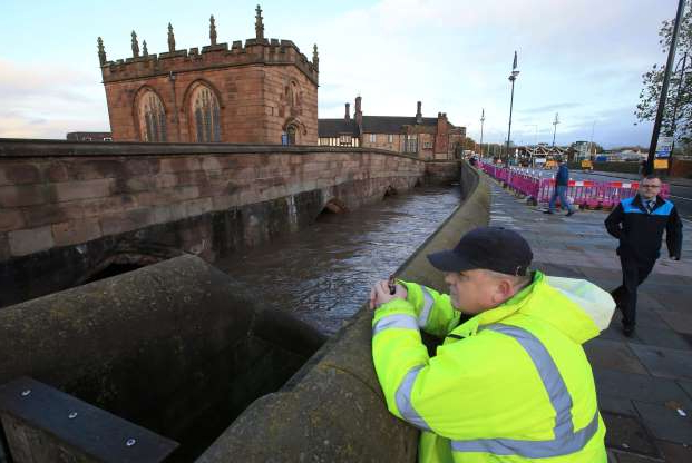 Man looks at Chantry Bridge, as it sits partially in floodwater in Rotherham, near Sheffield