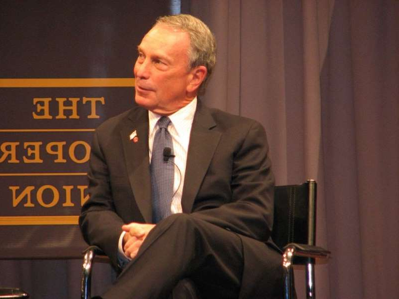 Michael Bloomberg wearing a suit and tie: Michael Bloomberg Is The Answer To A Question Nobody Is Asking