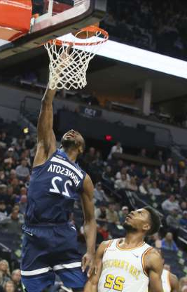 a basketball player in front of a crowd: Minnesota Timberwolves' Andrew Wiggins, right, lays up a shot under the watch of Golden State Warriors' Glenn Robinson III in the first half of an NBA basketball game Friday, Nov 8, 2019, in Minneapolis. (AP Photo/Jim Mone)
