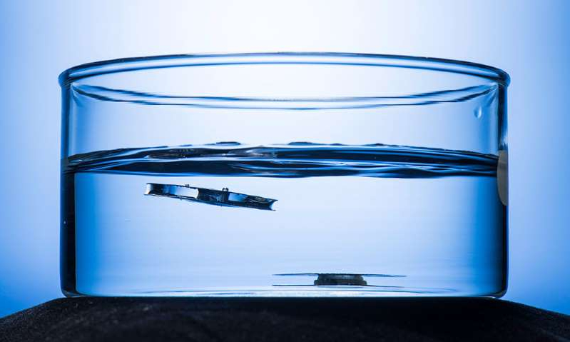 a glass with a blue background: fea-superhydrophobic-metal-unsinkable