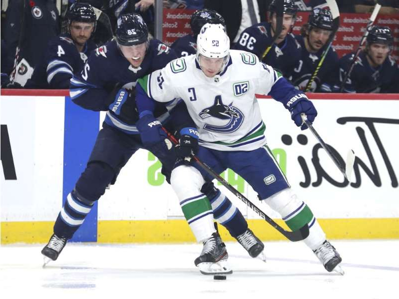 a group of hockey players on the field: Jets' winger Patrik Laine ties up Bo Horvat of the Vancouver Canucks during Friday's NHL action at Bell MTS Place in Winnipeg. The Canucks wrapped up a quick two-game road trip with a loss in the Manitoba capital.