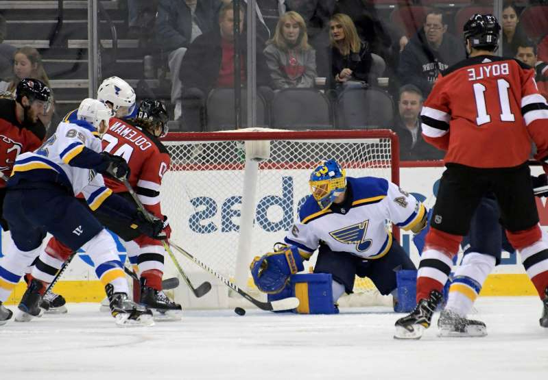 a group of hockey players on the snow: New Jersey Devils center Blake Coleman (40) scores a goal against St. Louis Blues goalie Jake Allen (34) during the first period of an NHL hockey game Tuesday, Nov. 7, 2017, in Newark, N.J. (AP Photo/Bill Kostroun