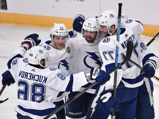 a group of people posing for the camera: Tampa Bay Lightning's Victor Hedman (77). Alex Killorn (17) and Nikita Kucherov (86) celebrate after an NHL hockey game against the Buffalo Sabres in Globen Arena, Stockholm Sweden. Friday. Nov. 8, 2019. (Anders Wiklund/TT via AP)