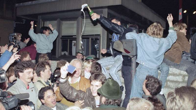 a group of people sitting in front of a crowd: East and West Berliners mingle as they celebrate on East Berlin territory on November 10, 1989, during the opening of the borders to the west.