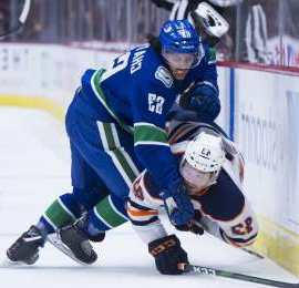 a hockey game in the snow: Vancouver Canucks defenceman Jalen Chatfield puts Edmonton Oilers right wing Josh Currie (43) into the boards during first period NHL preseason action in Vancouver, Tuesday, September, 17, 2019.