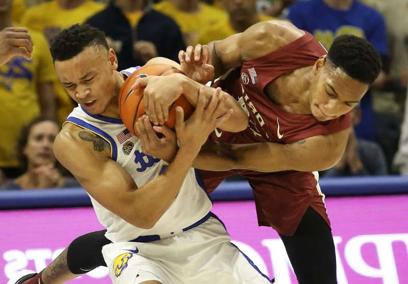 a man standing in front of a crowd: Florida State Seminoles guard Devin Vassell (left) and Pittsburgh Panthers guard Trey McGowens (right) fight for the ball during the second half at the Petersen Events Center on November 6, 2019.