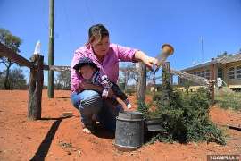 a man that is standing in the dirt: Queensland farmer Kate Stokes (pictured with three-month-old son Tom) said she checks her rain gauge regularly