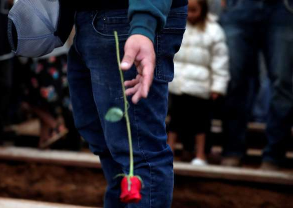 A mourner drops a red rose into a freshly dug grave at the cemetery in Colonia Le Baron, Mexico, Friday, Nov. 8, 2019, during the burial service for Rhonita Miller and four of her young children who were murdered by drug cartel gunmen. The bodies of Miller and four of her children were taken in a convoy of pickup trucks and SUVS, on the same dirt-and-rock mountainous road where they were killed Monday, for burial in the community of Colonia Le Baron in Chihuahua state. (AP Photo/Marco Ugarte)