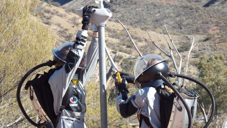 a person riding on the back of a bicycle: Simulation astronauts installing a weather station in Arkaroola in outback South Australia. (Supplied: Mars Society Australia and Saber Astronautics)
