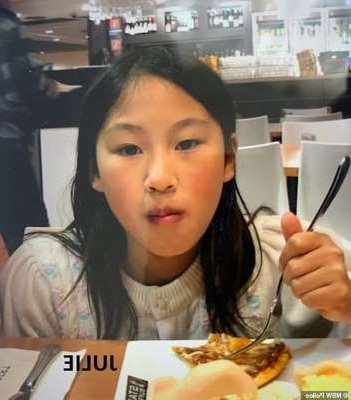 a person sitting at a table eating pizza: Julie Zhang (pictured), 11, was with her sister when the pair went missing on Friday
