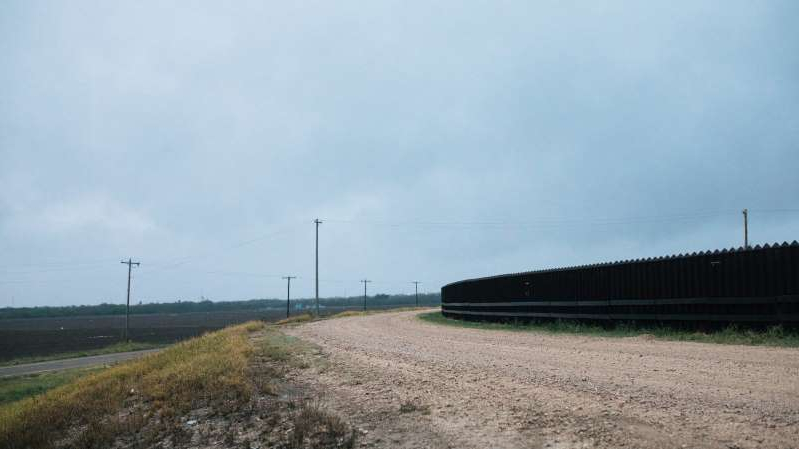 a train traveling down train tracks near a field: Of the 277 river miles in the Rio Grande Valley sector, only 55 miles have a physical barrier.