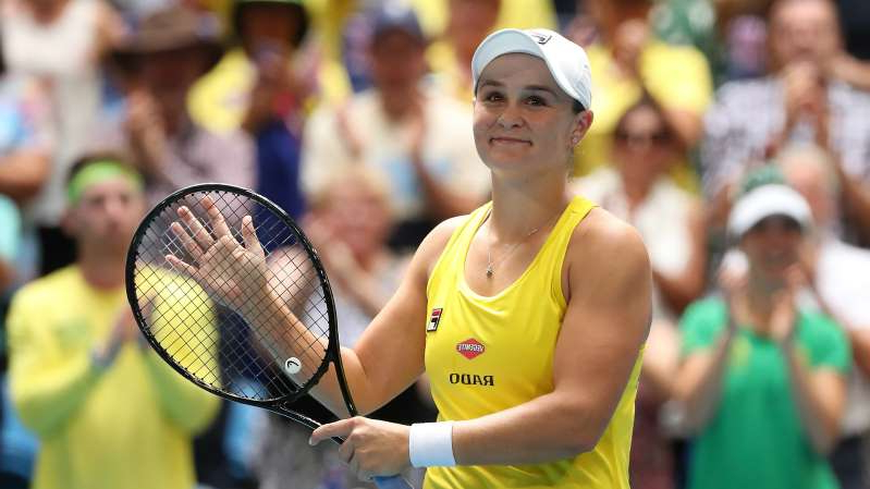 Ashleigh Barty holding a racket on a court: Ash Barty celebrates her Fed Cup win