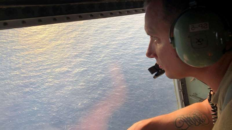 Tech. Sgt. Brett Corriveau, 39th Rescue Squadron loadmaster, scans the waters of the Gulf of Mexico from the inside of an HC-130P/N Combat King aircraft for any sign of the missing Airman from the 24th Special Operations Wing.