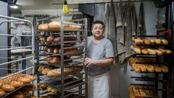 "a man cooking hot dogs on a grill: Jeannot Culeron at his bakery in Marigny-le-Lozon, France. ""When villages lose their bakery, they cry, 'What a tragedy!'"" he said. ""But they have to be willing to walk the talk."""