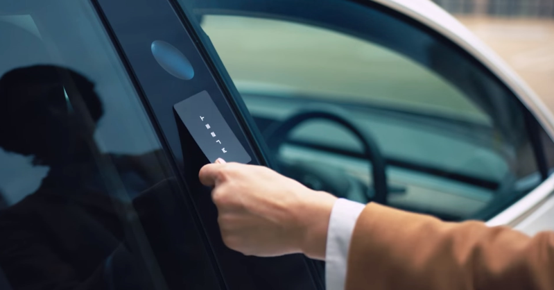 a person driving a car: Tesla Model 3 owners do not receive traditional car keys or fobs. Instead, the automaker provides them with a keycard and smartphone app to gain access and operate the car.