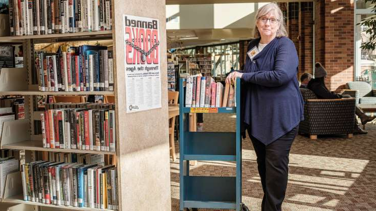 a person sitting in front of a book shelf: Bette Ammon, director of the Couer D'Alene Public Library, said she and other staff members have hunches about who might be hiding the books, but they have yet to catch anyone in the act.