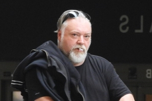 Kyle Sandilands, 48, denies he is dating personal assistant Tegan Kynaston, 33 - as the glum-looking radio star jets to LA following his split from Imogen Anthony