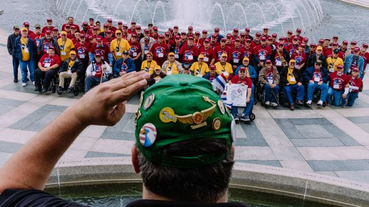 a group of people in front of a crowd: Veterans of the Korean and Vietnam wars that traveled on the Land of Lincoln Honor Flight at the World War II memorial in Washington.