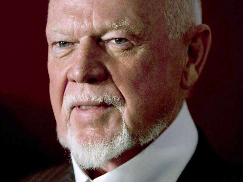a man wearing a suit and tie smiling and looking at the camera: Don Cherry, in his weekly Hockey Night in Canada segment, suggested new immigrants were not wearing poppies in the days leading up to Remembrance Day.