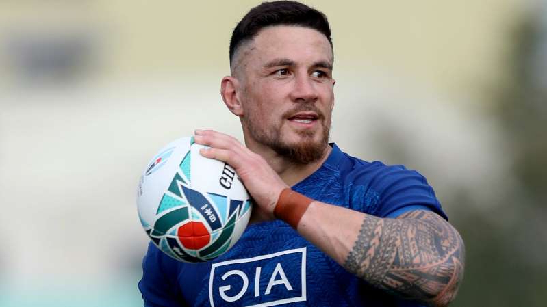Sonny Bill Williams in a blue uniform holding a football ball