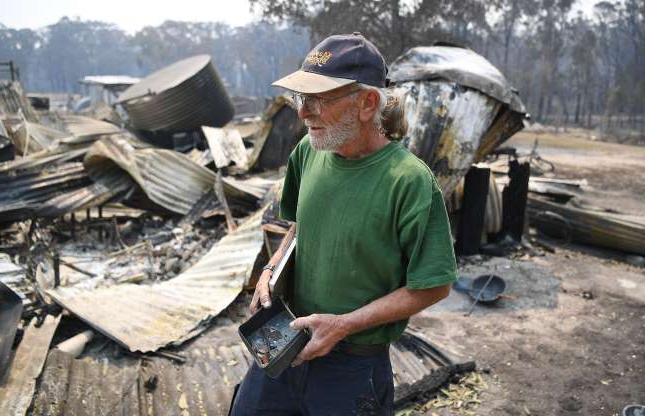 Thomas Eveans holds a burnt out coin collection he found while inspecting the remains of his house which was destroyed by a bushfire in Torrington, near Glen Innes, Monday, November 11, 2019.