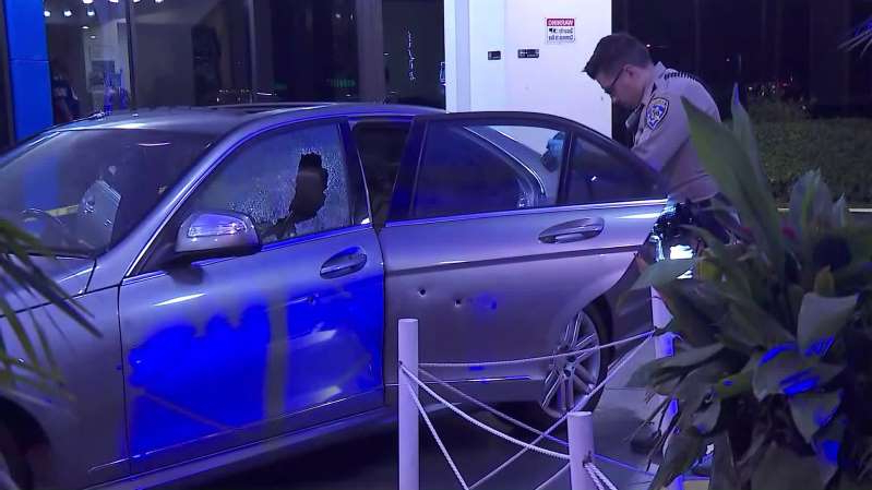 a man standing in front of a blue car parked in a parking lot: Officers investigate a car after it was involved in a shooting on the 405 Freeway in Inglewood on Nov. 11, 2019.