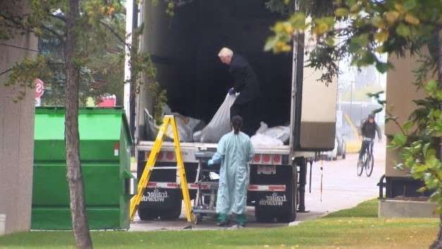 a man that is standing in the grass: A funeral home employee drags a dead person in a body bag out of a refrigerated trailer at the Office of the Chief Medical Examiner in Edmonton on Monday.