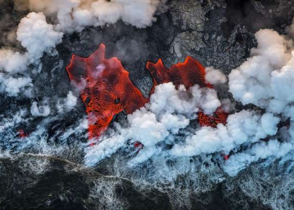 a pile of smoke: Spanish photographer Luis Villariño Lopez framed this shot through the door of a helicopter, capturing red-hot lava spewing from one of the world's most active volcanos, Kilauea, on Hawaii's Big Island.