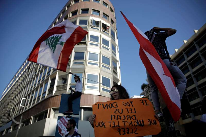 a sign on the side of a building: Protesters wave flags at a demonstration organised by students during ongoing anti-government protests in Beirut