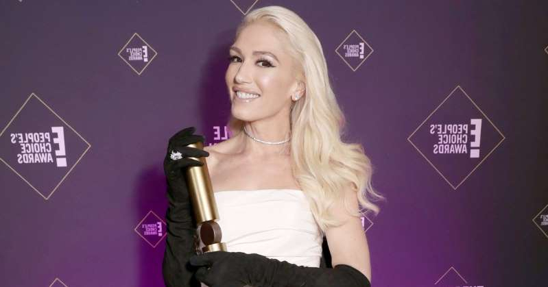 Gwen Stefani holding a sign posing for the camera: Gwen Stefani Denies Wearing Engagement Ring: 'When I Have Something to Say, I'll Say It'