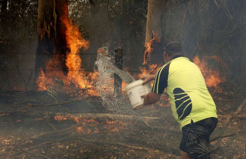 Jamie Fato tries to stop an out of control fire entering Owen Whalan's property at Koorainghat, near Taree in the Mid North Coast region of NSW, Tuesday, November 12, 2019.