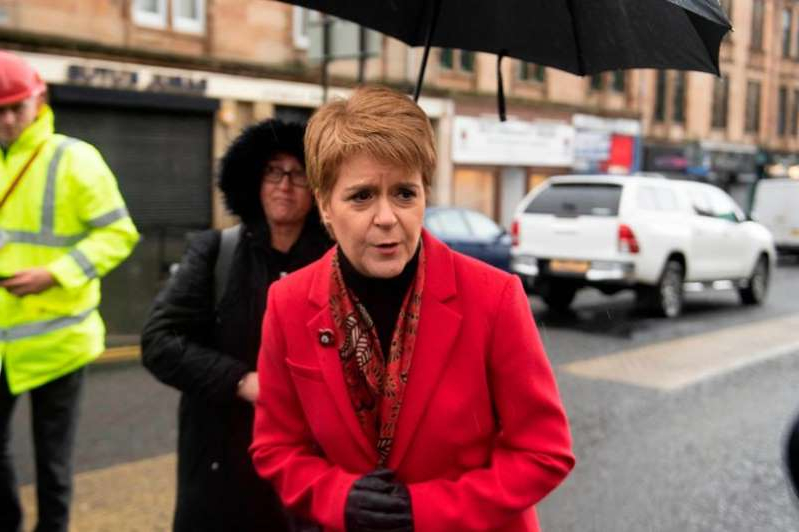 Nicola Sturgeon walking down a street holding an umbrella: First Minister Nicola Sturgeon at the scene