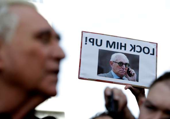 Slide 9 of 13: A protester holds up a sign as Roger Stone, right, a confidant of President Donald Trump, speaks outside of the federal courthouse following a hearing, Friday, Jan. 25, 2019, in Fort Lauderdale, Fla. Stone was arrested Friday in the special counsel's Russia investigation and was charged with lying to Congress and obstructing the probe. (AP Photo/Lynne Sladky)