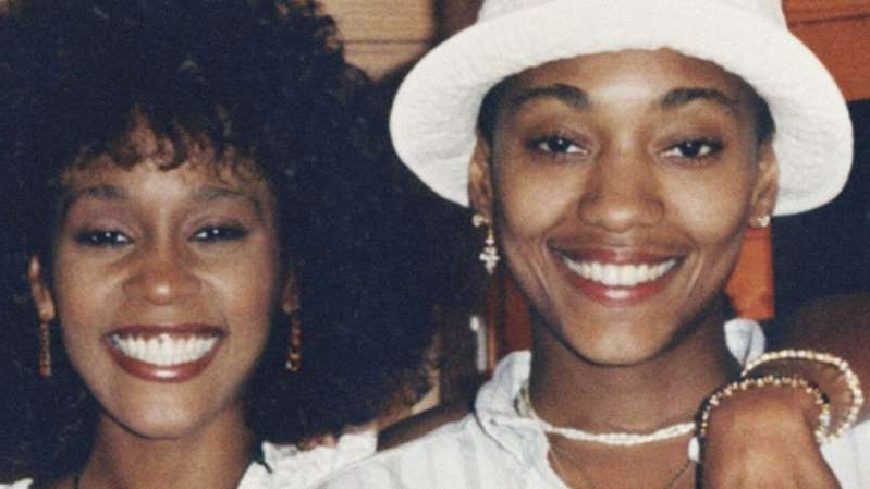 Whitney Houston wearing a hat and smiling at the camera