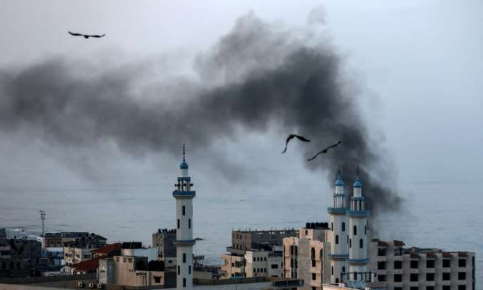 a bird flying over a body of water with smoke coming out of it: Smoke rises over Gaza City as Israel carries out a second day of air and missile strikes in response to barrages of rocket fire following its targeted killing of a top militant