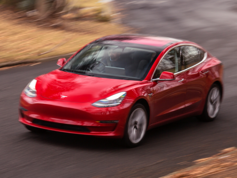 a red toy car on the road: A Tesla Model 3 sedan.