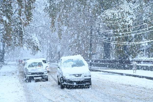 Slide 101 of 120: Cars covered in snow drive along a road during a first snowfall in Srinagar on November 7, 2019. (Photo by Tauseef MUSTAFA / AFP) (Photo by TAUSEEF MUSTAFA/AFP via Getty Images)