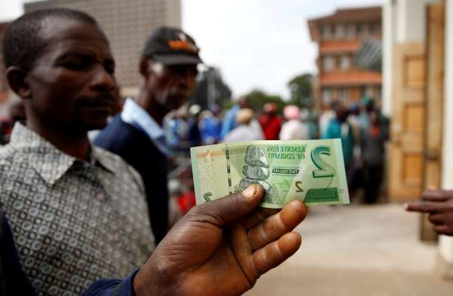 Slide 11 of 120: A man poses with Zimbabwe's new two dollar banknote as customers queue outside a bank in Harare, Zimbabwe, November 12, 2019. REUTERS/Philimon Bulawayo