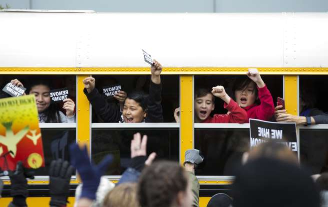 Slide 15 of 85: School students cheers to demonstrators as they pass by next to their bus during the march on Pennsylvania Av. protesting against climate policies and to impeach President Donald Trump, in Washington, Friday, Nov. 8, 2019.