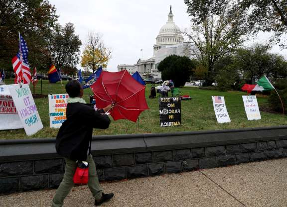 Slide 22 of 85: A women holds an umbrella as she walks past banners in front of the Capitol in Washington, U.S., October 31, 2019.