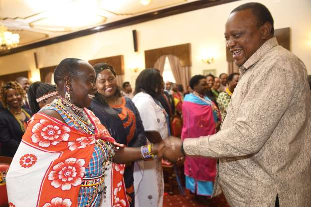 Slide 69 of 120: Kenya's President Uhuru Kenyatta (L), meeting with cultural leaders from different parts of the country, with prevalence of Female Genital Mutilation(FGM)at the State House in Nairobi, on November 8, 2019. - President Kenyatta promised to end FGM by the year 2022, where the practice is prevalent mostly in pastoral communities. (Photo by SIMON MAINA / AFP) (Photo by SIMON MAINA/AFP via Getty Images)