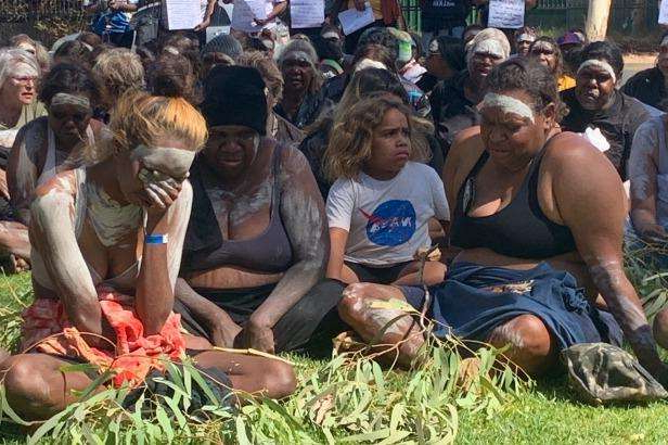 a group of people standing in front of a crowd: Local members of the community mourn the death of Warlpiri man Kumanjayi Walker in Alice Springs on Thursday.