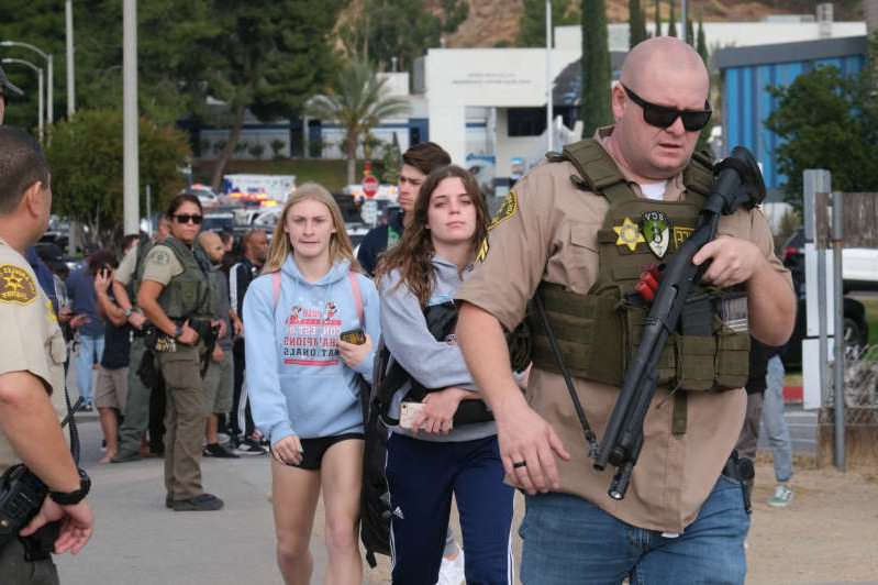 a group of people standing on a sidewalk: Students are escorted off of campus at Saugus High after a shooting occurred around 7:30 at Saugus high in Santa Clarita, CA Thursday, November 14, 2019.    (Photo by David Crane, Los Angeles Daily News/SCNG)